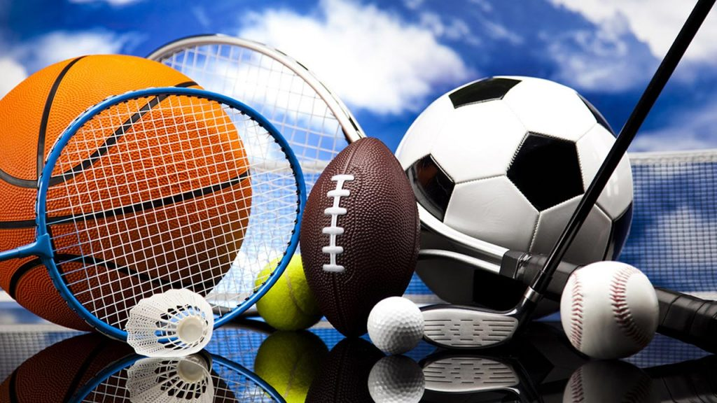 Multiple sports balls and equipments in a pile with a background of clouds and blue skies.