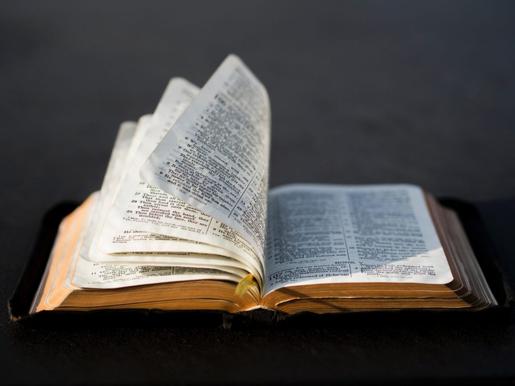 Opened Bible with wind lifting up pages