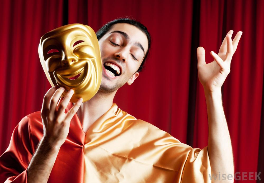 A male actor holding an acting mask  in front of a red curtain