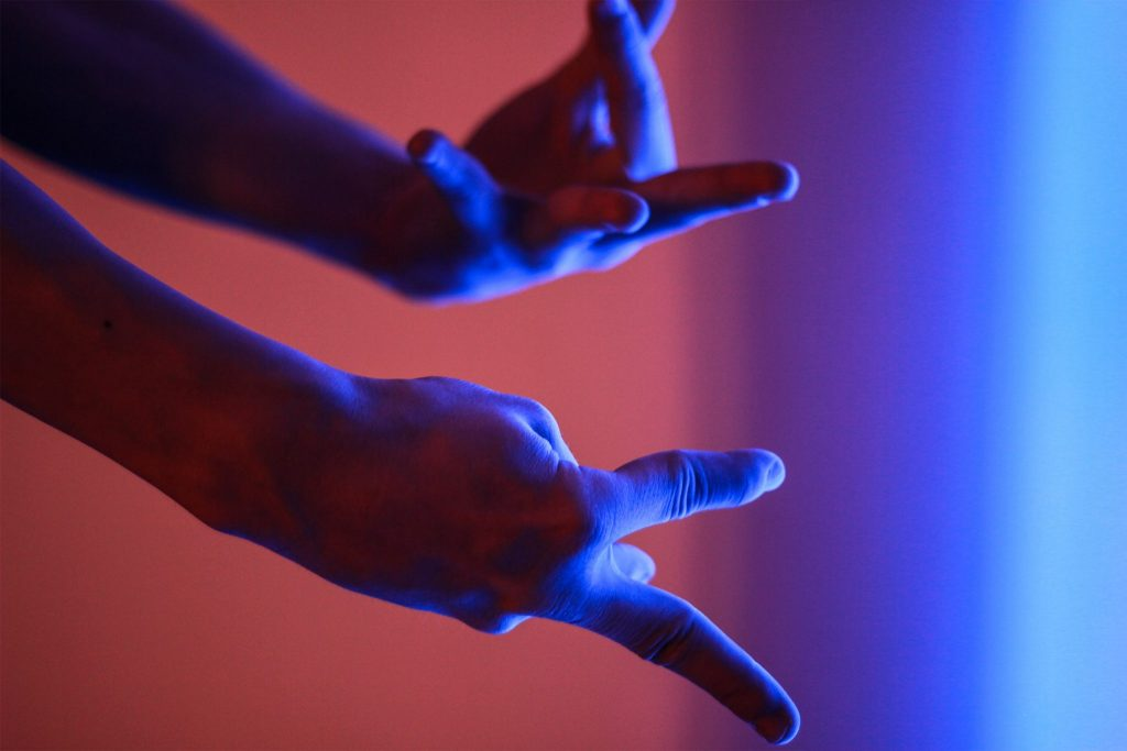 Hands doing American Sign Language (ASL) in front of a red and blue background