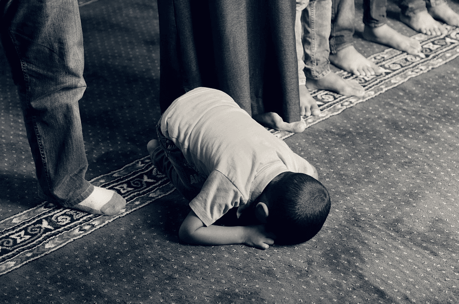 child praying on a mat, bowing down