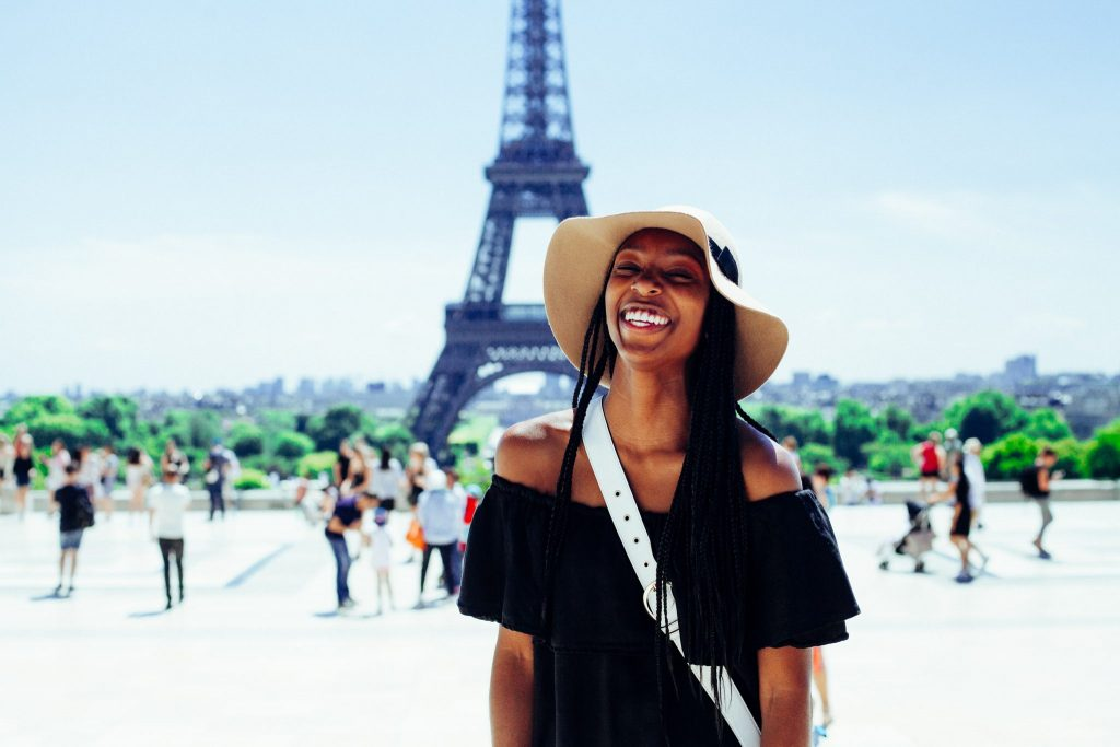 Woman standing in front of the Eiffel Tower in Paris during the daytime