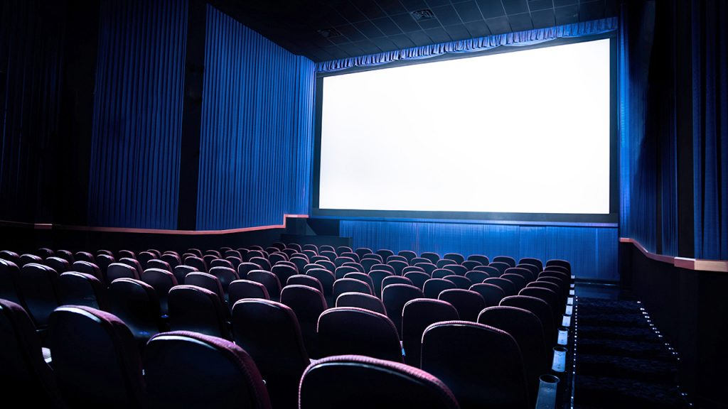 A cinema hall with a wide screen and  seats