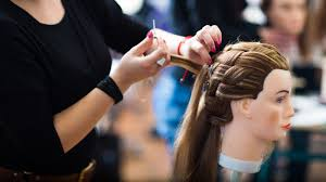 A cosmetologist practicing a hairstyle on a mannequin