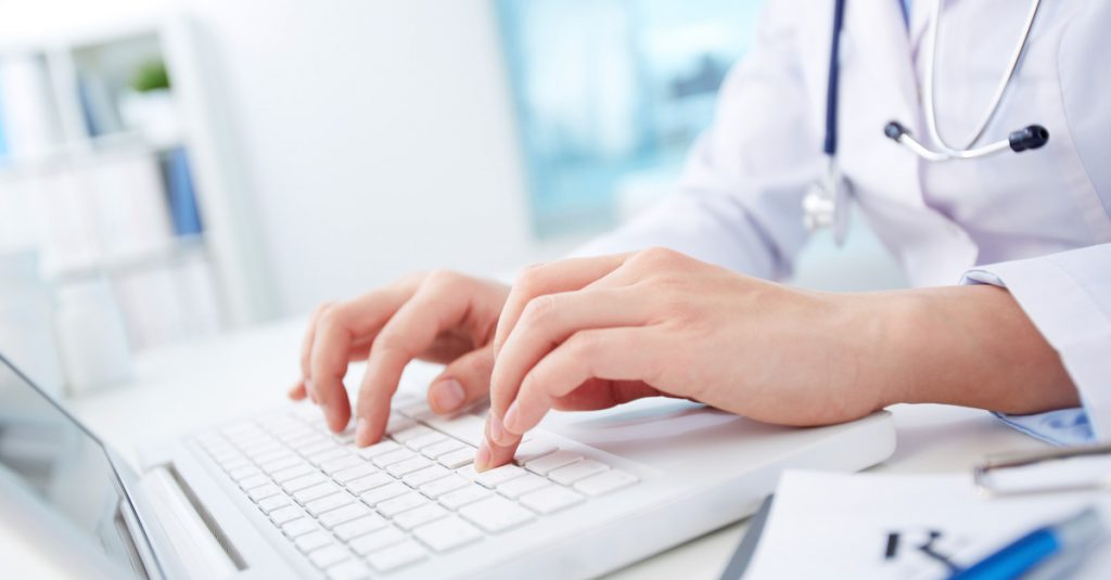 a doctor inputting information into a computer
