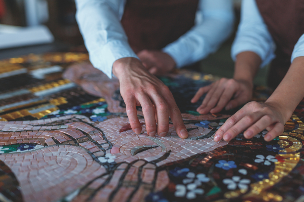 A close-up image of people working on a mosaic piece.