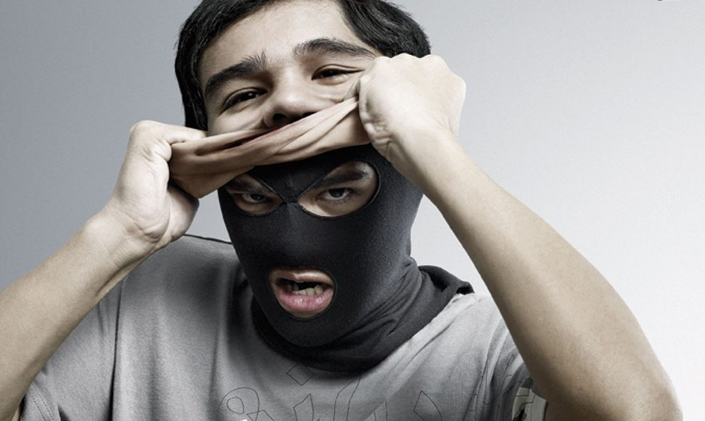 man revealing ski mask underneath (represents criminal mind)