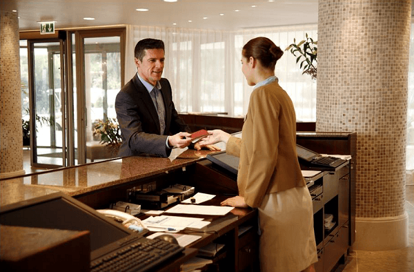 customer talking to a person at a front desk at a hotel