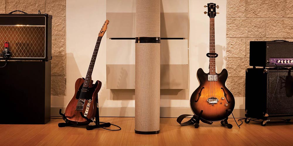 Two guitars in a studio with other music equipment