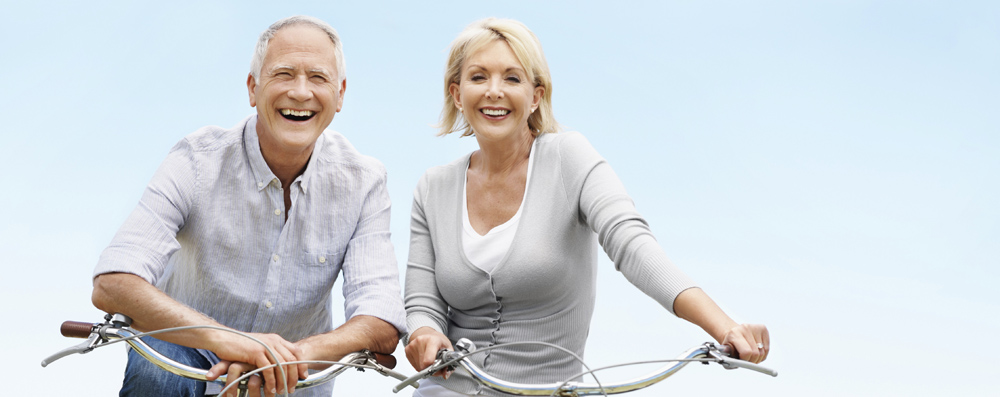 Two elderly people leaning on bicycles