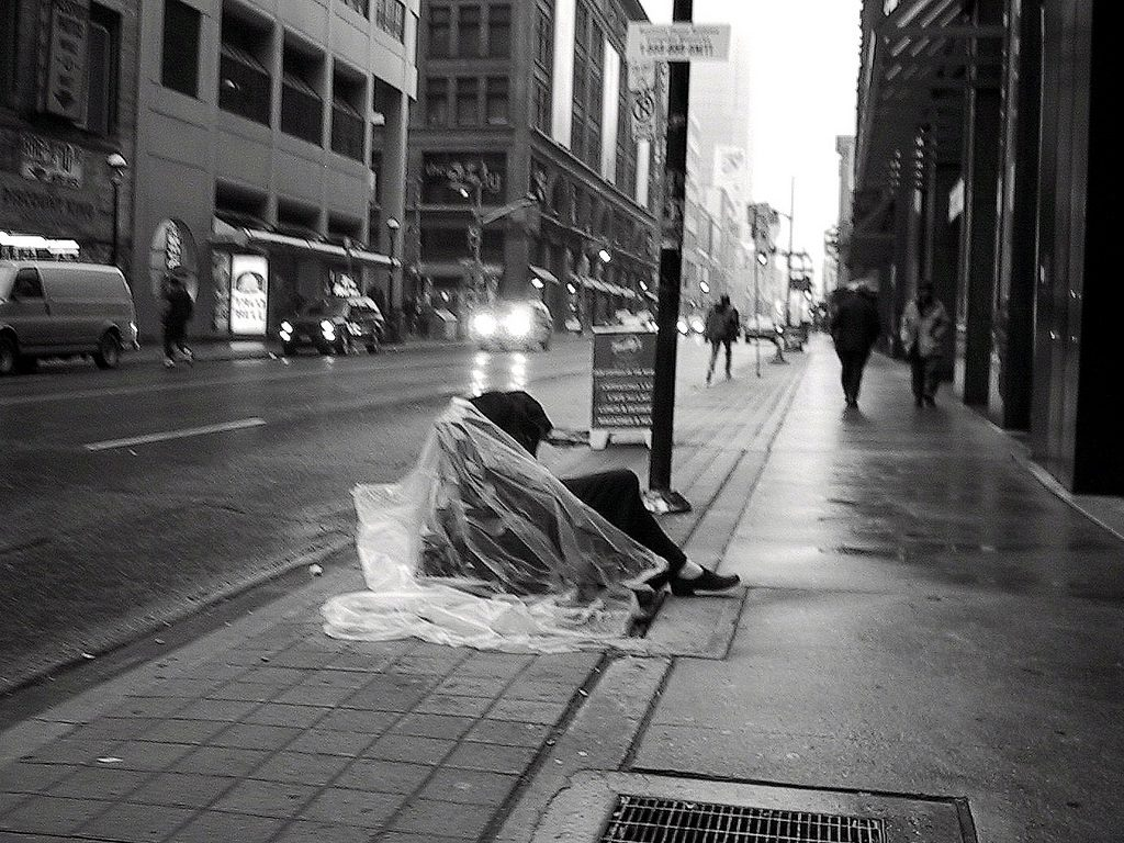 A homeless person sitting on a city sidewalk with a bag around their body.