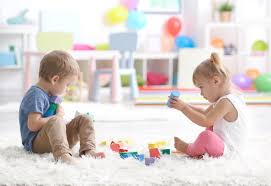 Two toddlers playing with toys on a floor
