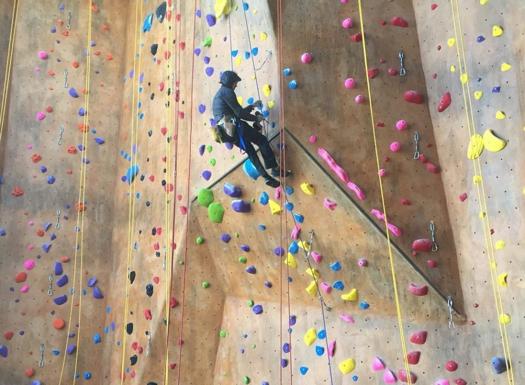 man climbing in indoor rock climbing gym