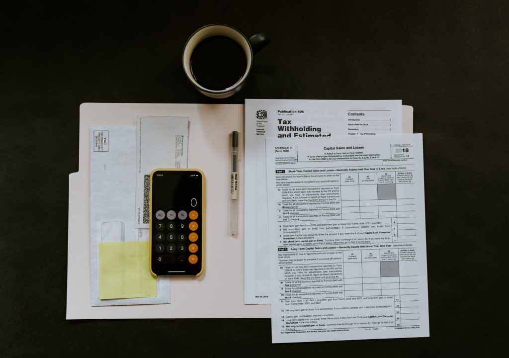 Tax papers with a phone open to the calculator app and a cup of coffee