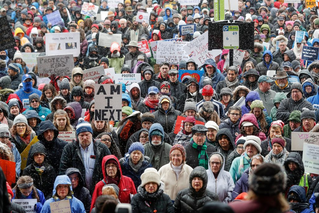 An image of people marching and holding signs at a protest.