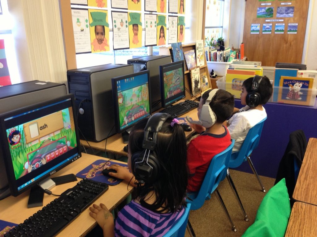 Three young students sitting and playing an educational game on a computer.