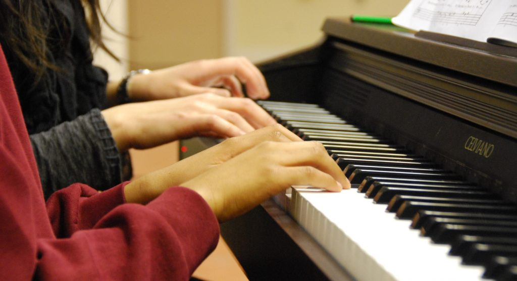 A picture of two people playing a piano.