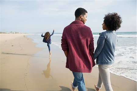 A picture of two people holding hands and walking along a beach.