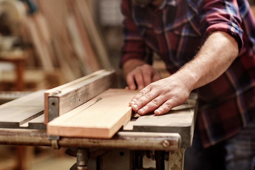 man holding piece of wood in a woodshop station