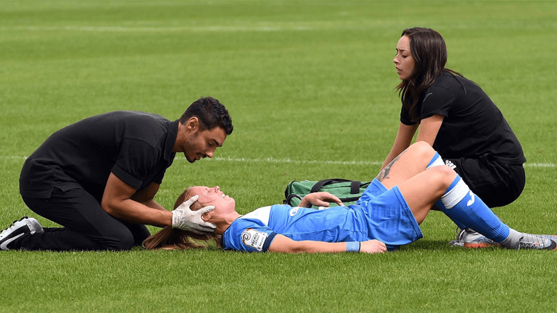 Two first aid personnel attending to a female athleteon a soccer field
