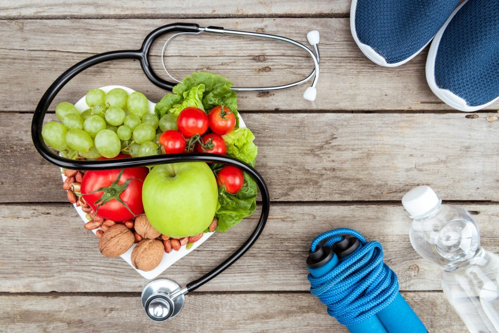 A Stethoscope, a bowl of fruits, a skipping rope, a bottle of water and a pair of sneakers