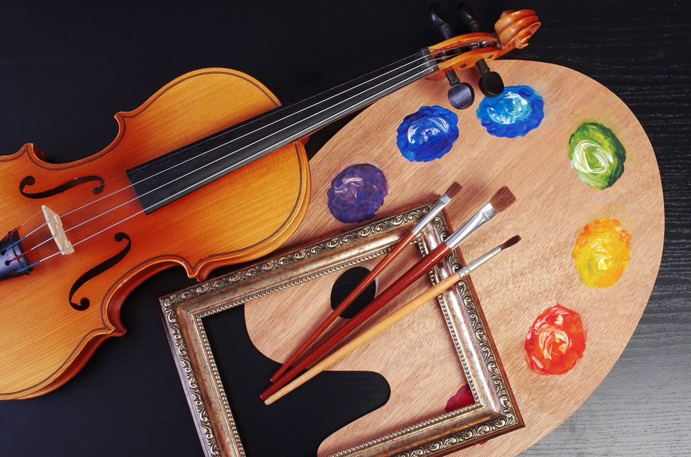 picture of a violin, a picture frame, paintbrushes, and paint