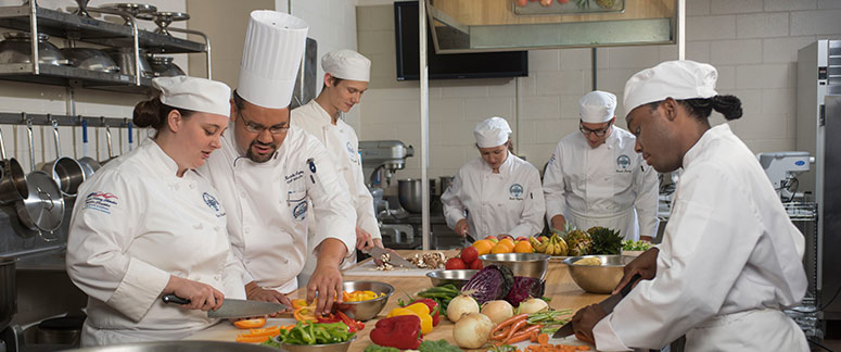 A group picture of culinary art students busy with food preparation.