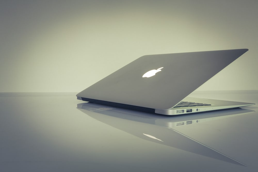 A laptop half-opened on a reflective white table