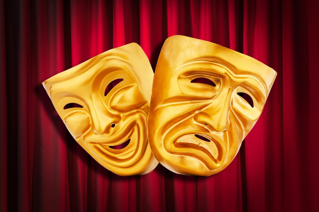 Two acting masks in front of a theatre curtain