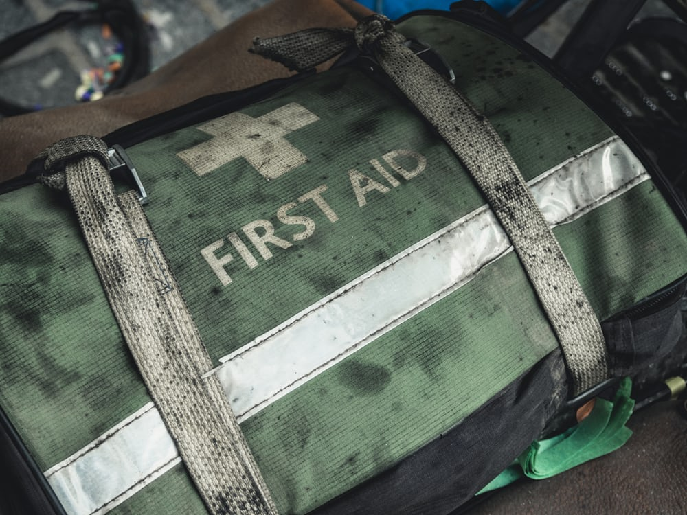 Green first aid duffle bag with a white stripe