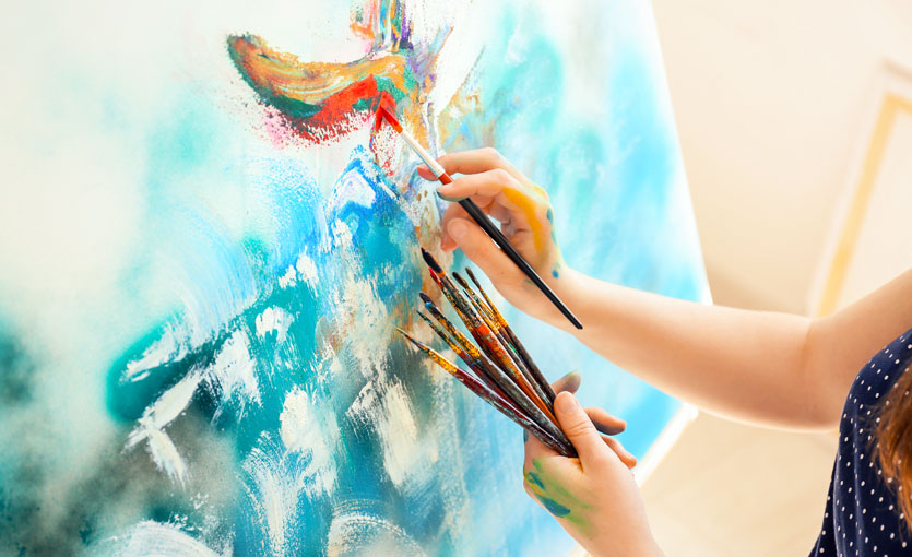 A painter holding brushes in one hand while painting with the other