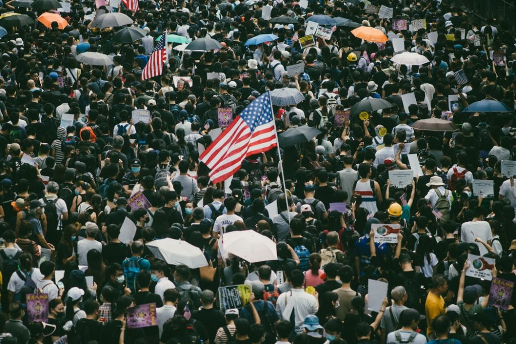 Crowd with American flags and umbrellas