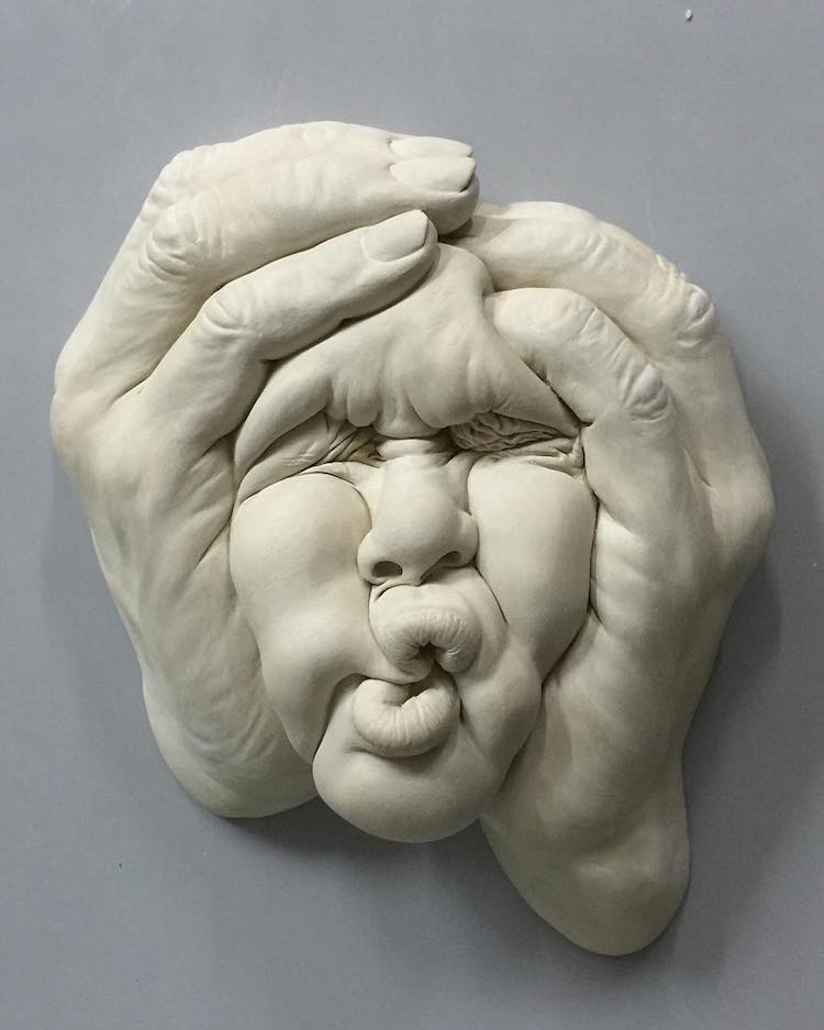 A ceramic sculpture of a human face and hands