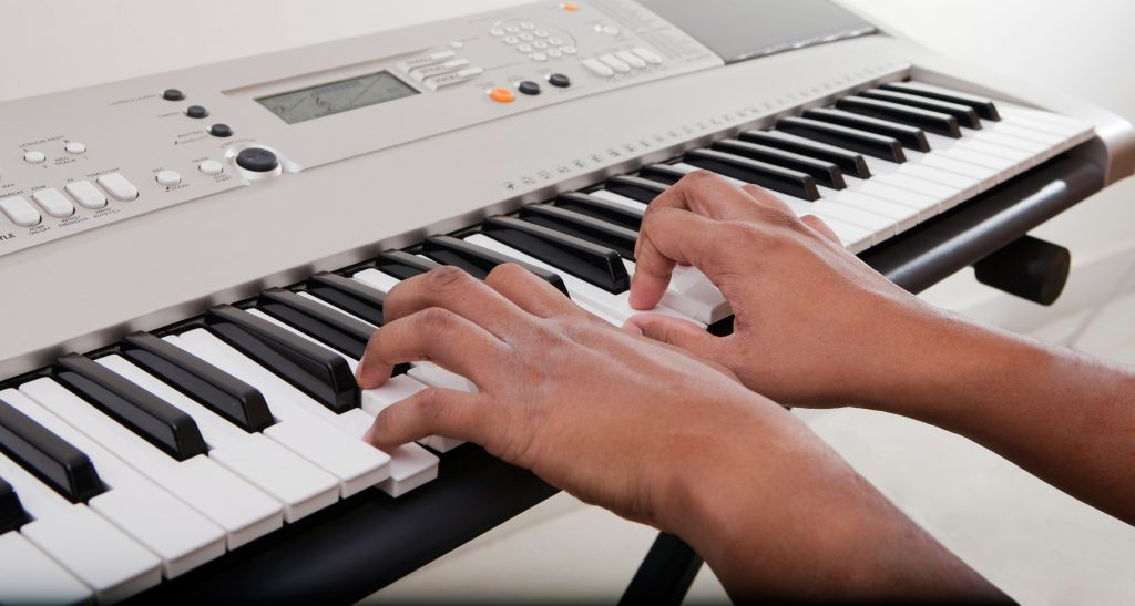 A persons hands playing the keyboard