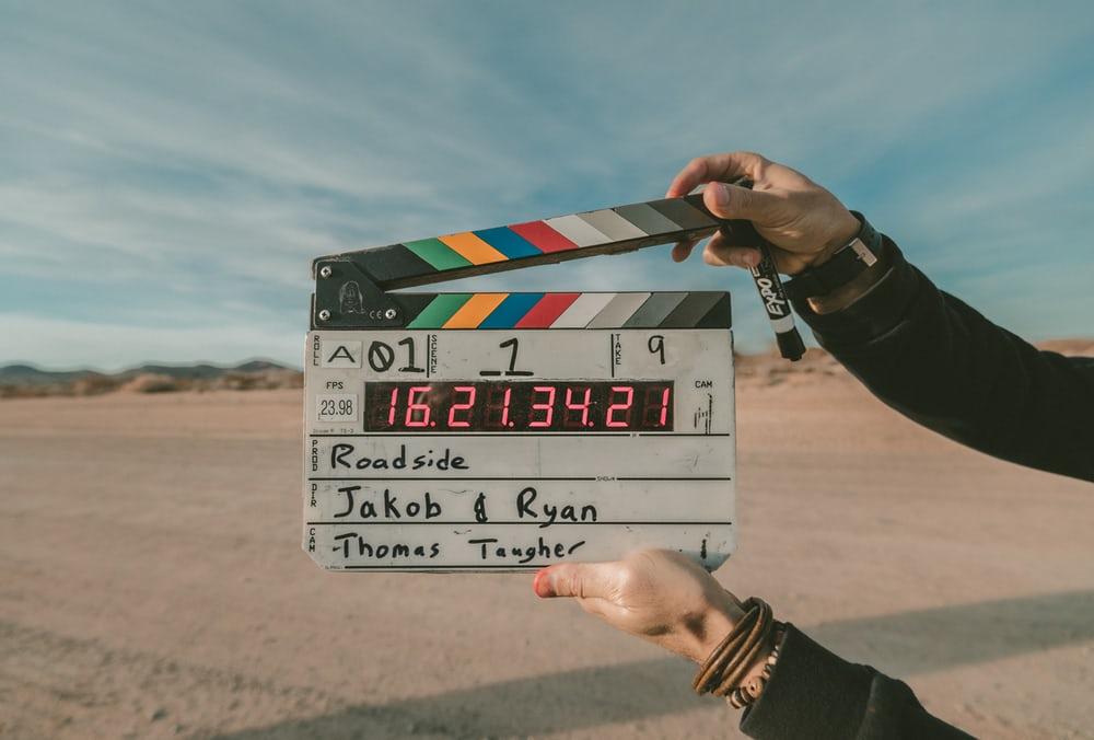 Hands holding a clapboard over a desert background