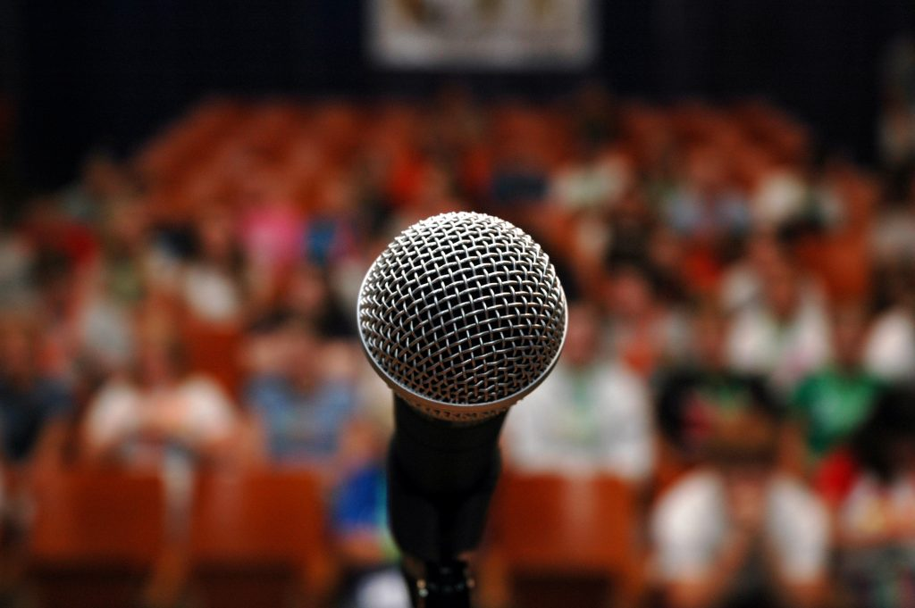 A microphone on a stage in front of an audience