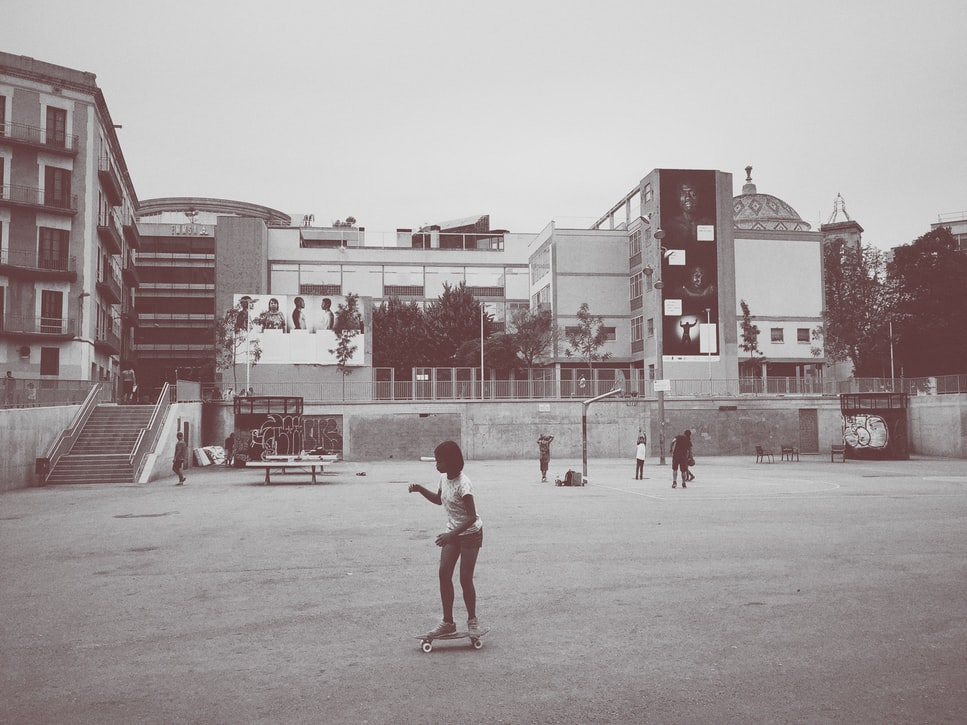 Children playing in an urban schoolyard, in a black and white picture