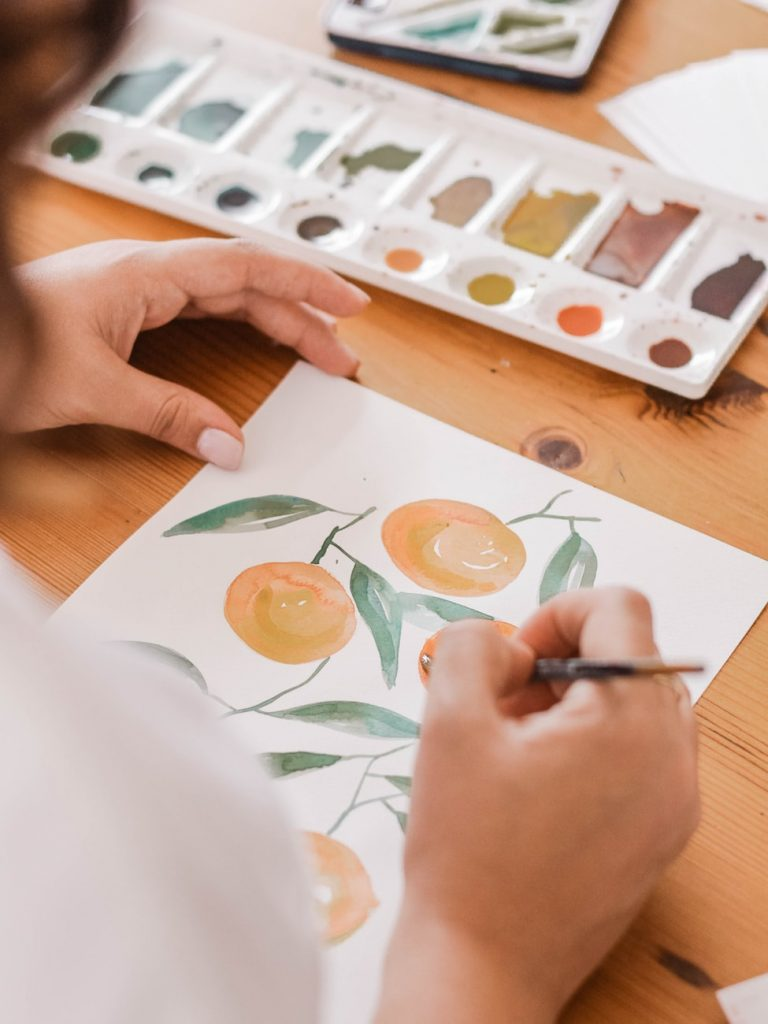person painting watercolor of oranges