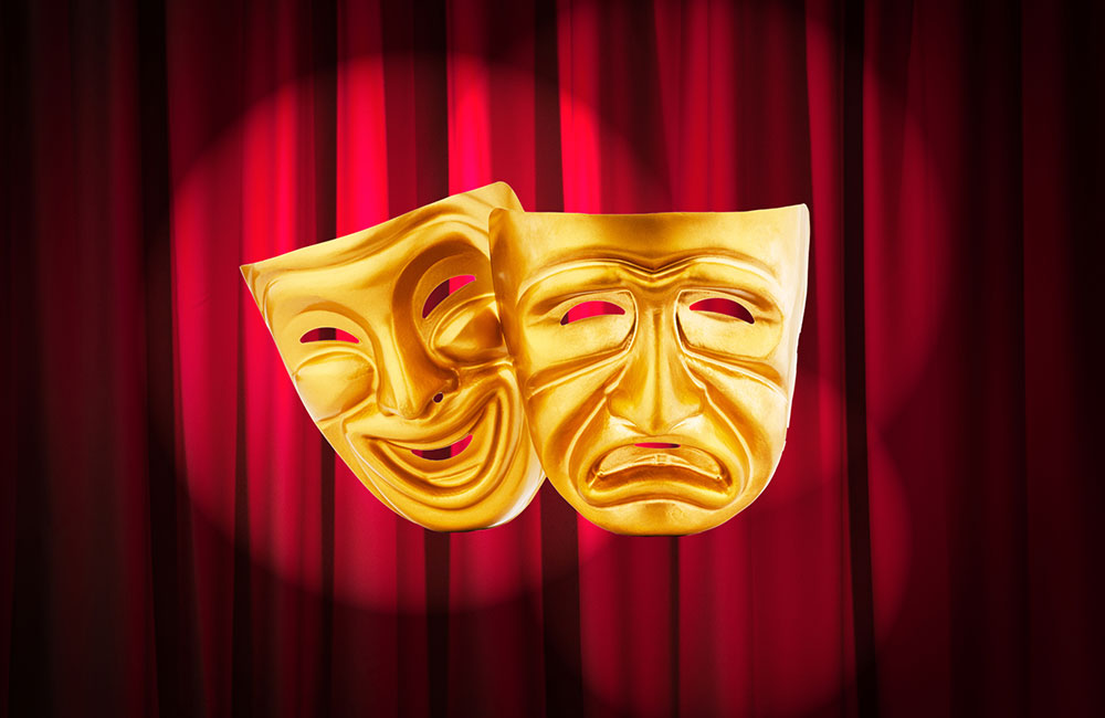 Two acting masks in front of a maroon theatre curtain