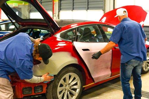 Two men working repairing a car's body