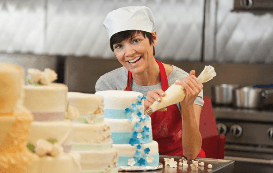 A pastry chef decorating a cake