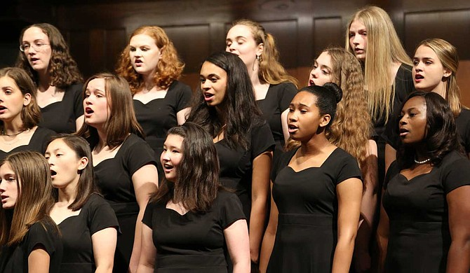 A women's choir performing on stage