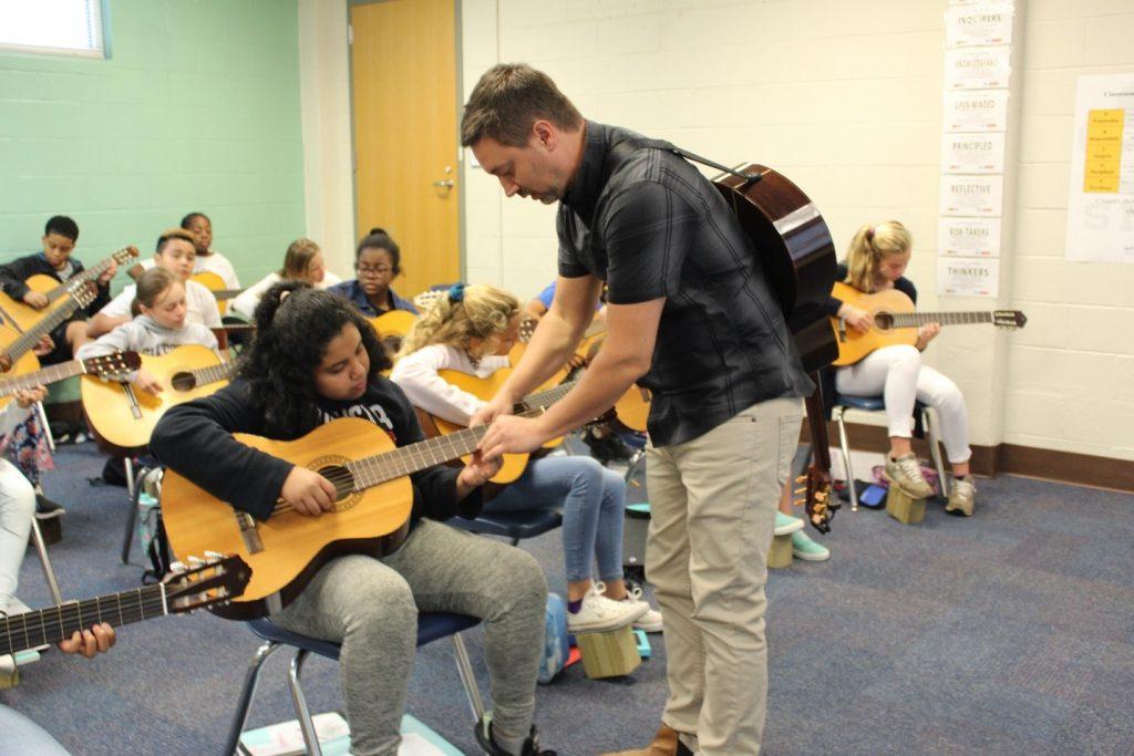 A music instructor teaching a guitar class