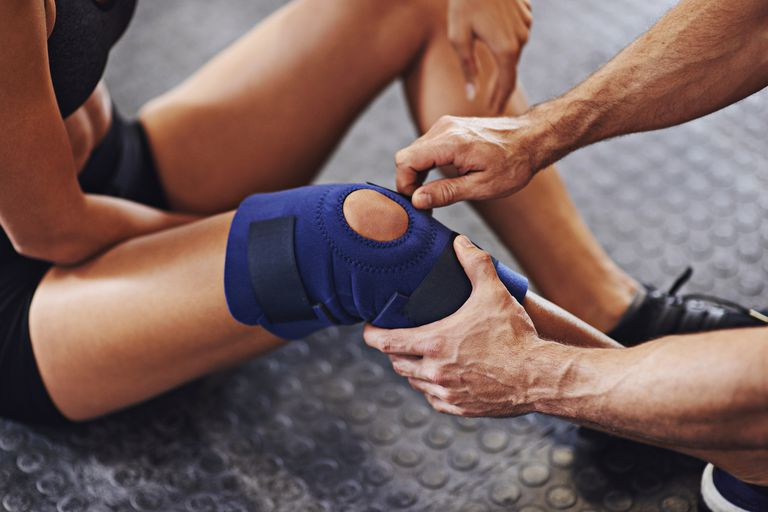 A sports physician attending to an athlete's knee