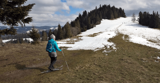 a concept of a woman skiing on a grassland while snow is receding