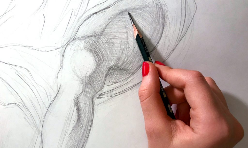 An artist drawing on a piece of paper
