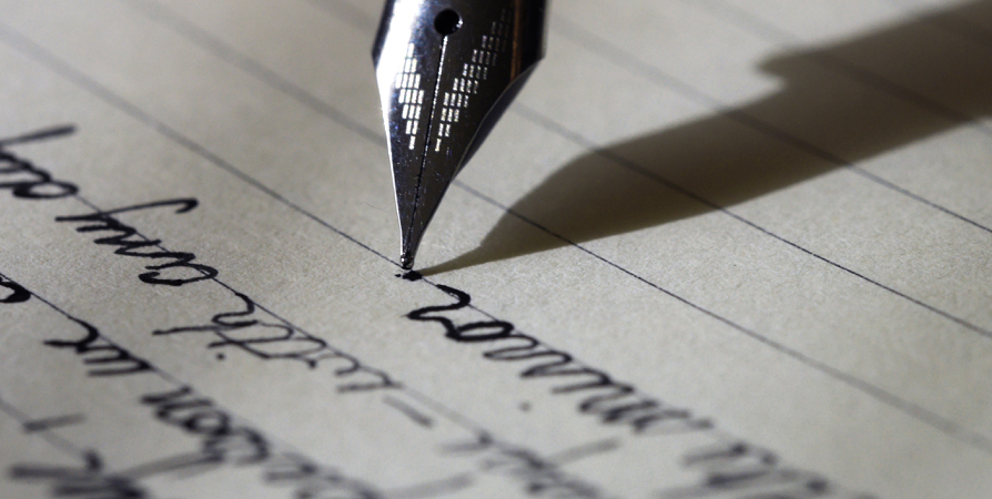 A pen with black ink writing on a paper