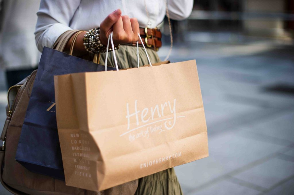stylish lady holding shopping bags of clothes and apparel