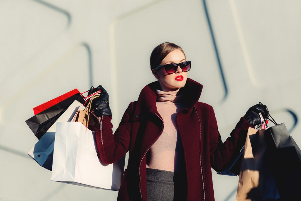 female student going shopping and holding shopping bags of clothing and apparel from a mall