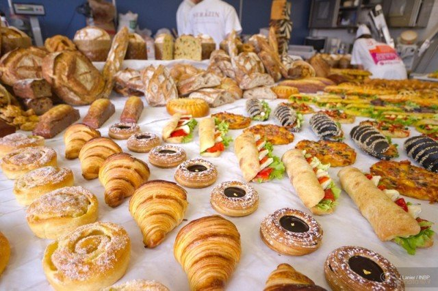 An assortment of baked cakes, bread, and donuts on a table